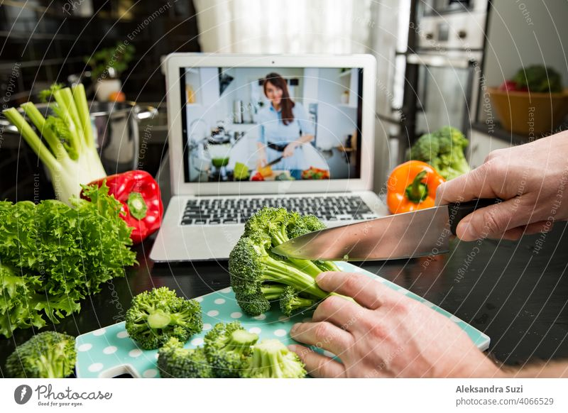 Beautiful happy woman streaming broadcast video blog about tasty and healthy food from home kitchen. Healthy lifestyle and social media. Man watching video recipe on laptop and cooking at home.