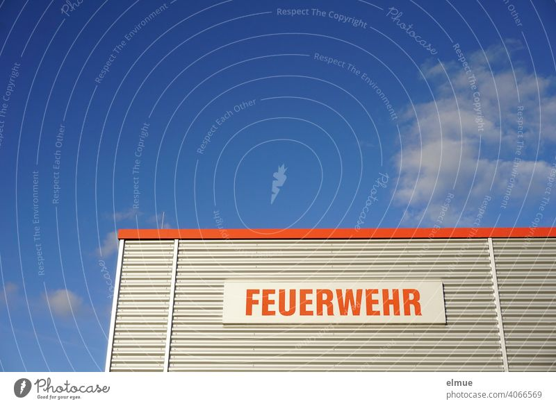 """Partial view of a functional building with metal cladding and the inscription in red """"FEUERWEHR"""" in front of a blue sky with fair weather clouds / rescue service / emergency call 112"""