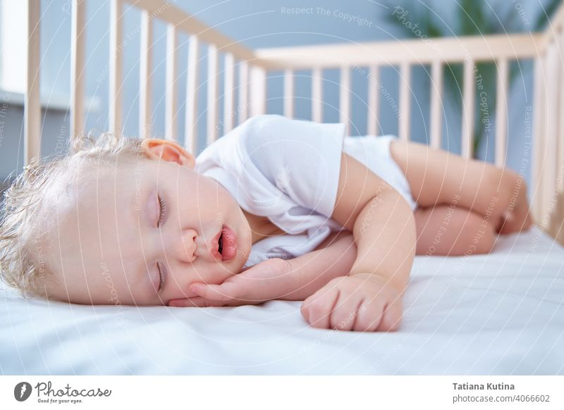 Baby sleeps in baby wooden crib for newborns. A spacious, bright room with a date palm tree in the background. Copy space toddler infant bed bedding kid