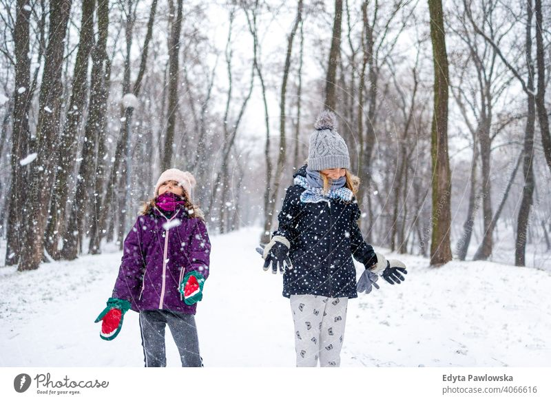 Children throwing snow in the air and enjoying a cold winter day daughter two laughing friends enjoyment activity playful kids smiling snowflakes together