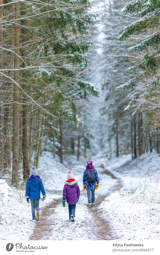 Mother and children enjoying a walk through the woodland together in winter outdoors family kids adventure active tourist girl female woman activity person