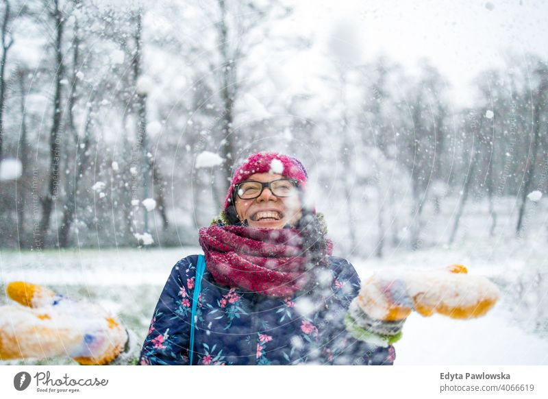 Woman throwing snow in the air and enjoying a cold winter day glasses outside natural healthy mitten scarf trees gloves one snowflake christmas beauty hat