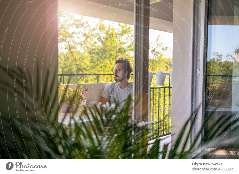 Man drinking coffee on the balcony of his apartment fresh air rest quarantine potted plant stay at home glasses lockdown simple life terrace healthy lifestyle