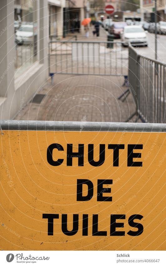 In front of a barrier, a yellow sign in French reads CHUTE DE TUILES Roofing work or storm damage Chute de Tuiles Storm damage cordon Yellow off Exterior shot