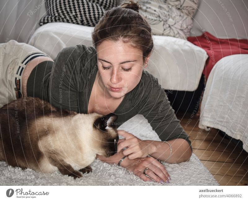Young woman cuddles her Siamese cat lying on the floor Cat Pet Cozy at home Stroke Caress Cuddling Lifestyle relaxing Relaxation stay at home