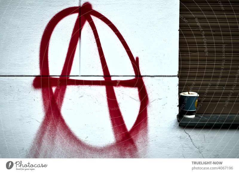 A sprayer has sprayed the well-known signet of the anarchists or anarchos on a white house wall, large and in red color: large A in a circle. The coffee mug on the windowsill next to it in front of a closed brown shutter seems appropriate