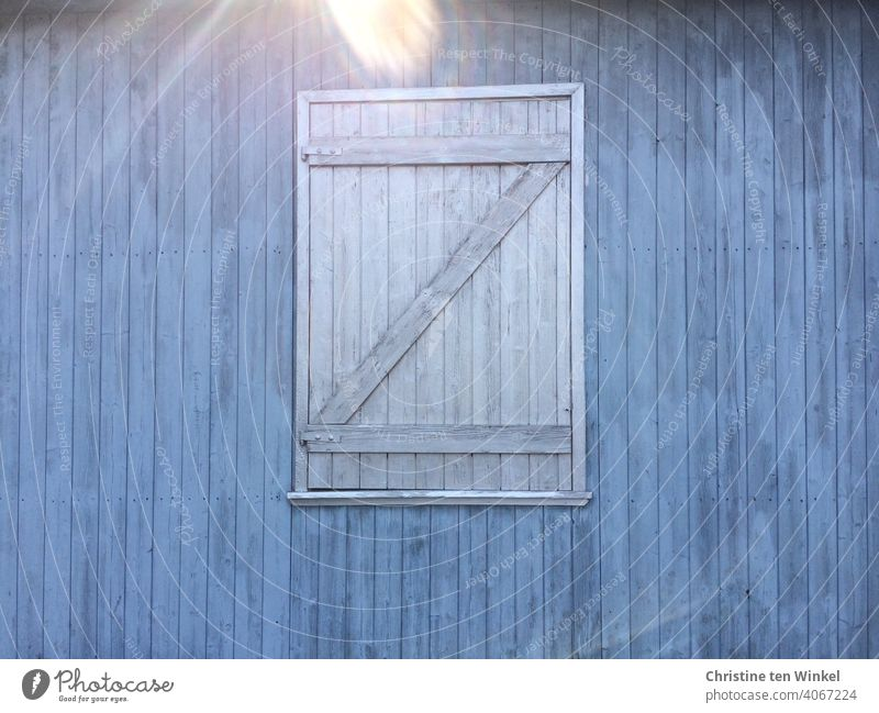 Blue wooden facade with grey closed wooden shutter. Reflection by incident sunlight at the upper edge of the picture Wooden facade Shutter Closed too Facade
