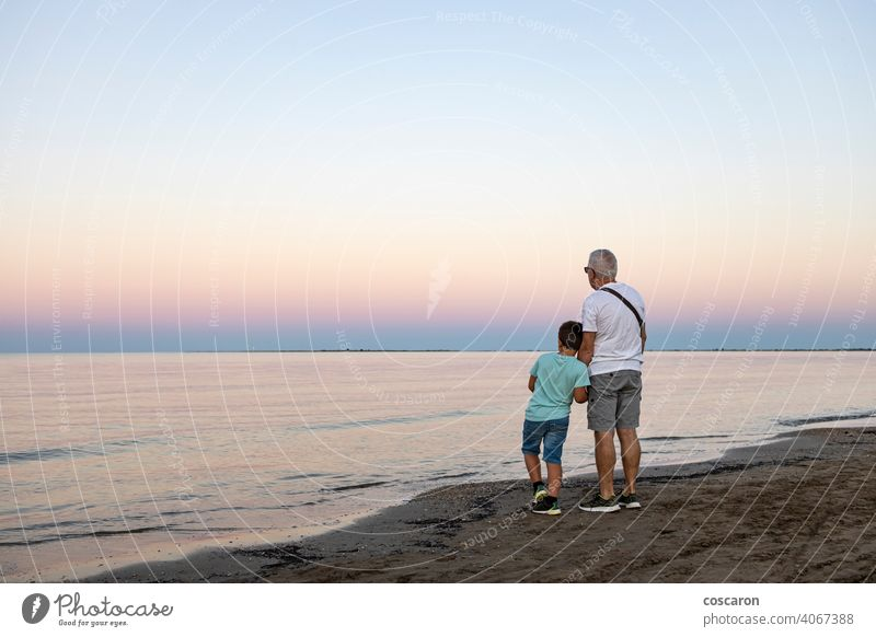 Grandfather and his grandson looking the ocean at sunset beach boy child childhood coast dad evening family freedom fun generation golden grandchild grandfather