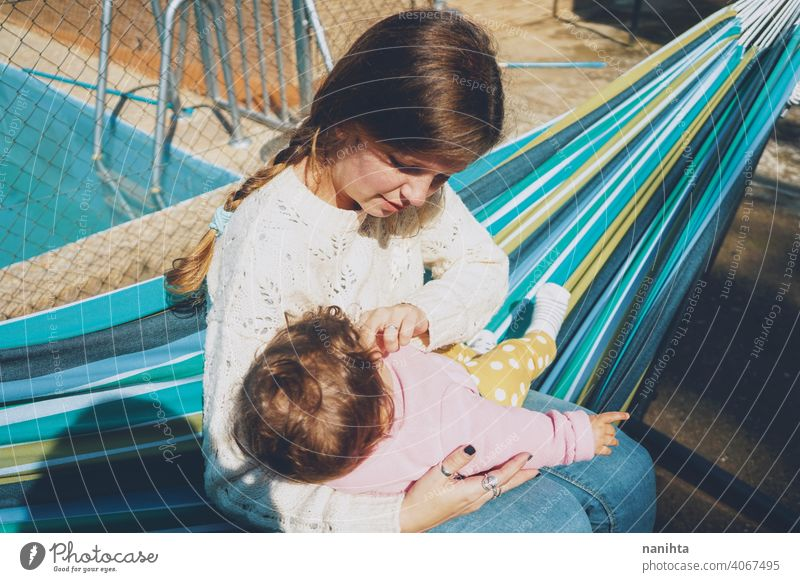 Young woman caring her baby sitting on a hammock mom family holidays care love home outdoors day care pool hug daytime routine happiness lovely cute babyhood