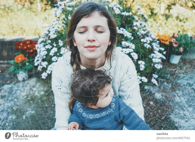 Young mom hugging her baby and enjoying a spring day in the garden family lifestyle love care child kid childhood springtime flowers nature natural hippie