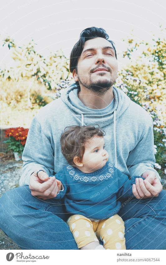 Young dad enjoying a sunny day with his baby in the garden father family love happiness yoga meditation breathing exercises care caring parenting lovely cute