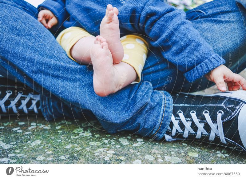Close up of body parts of a baby of teenage fathers with her dad parent feet legs foot close close up casual sneakers barefeet teenage parenting family