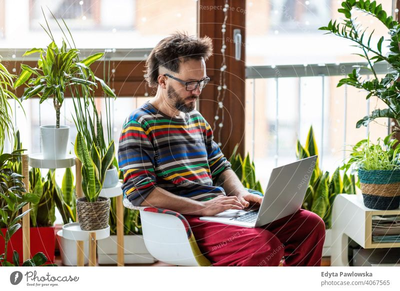 Young man working at home with laptop surrounded by houseplants online online banking online learning online shopping office hand freelance mobile keyboard