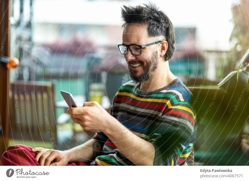 Happy man using a mobile phone at home work freelancer blogger guy call texting online caucasian electronic network digital customer retail shop touch finger