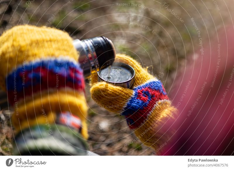 Hands in colorful mittens pouring a hot drink from thermos winter warm Scandinavian gloves woodland weather hike female flask weekend activities cold bottle