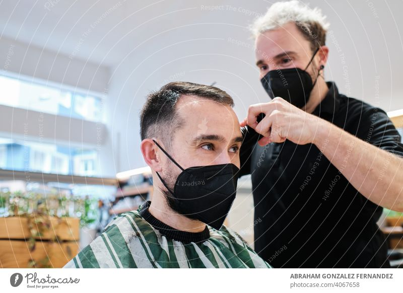 hairdresser cutting a customer's hair, with protective masks stylist haircut woman salon style facemask protection beauty hairstylist barber hairstyle