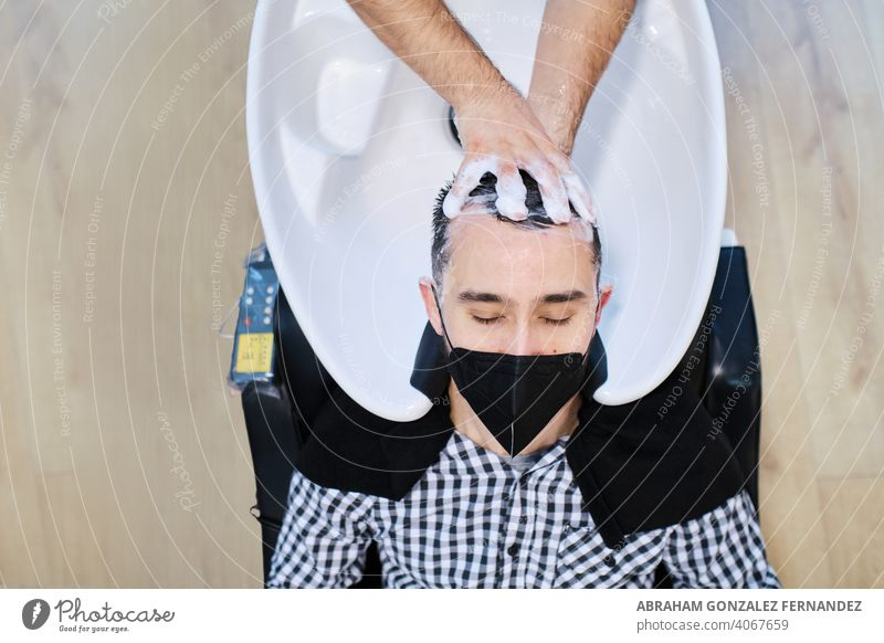 client with protective face mask washing hair in a hairdresser's salon shampoo beauty man barber sink stylist person top view service hairstyle professional