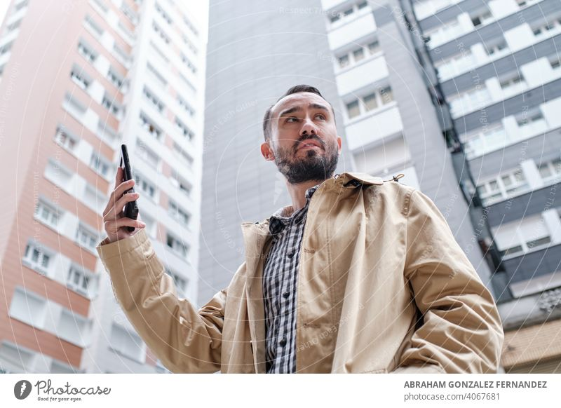 businessman holding a mobile phone in his hand between buildings person communication technology smart phone internet telephone connection horizontal show
