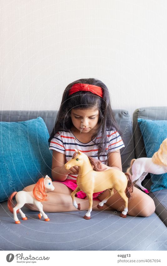 Little girl playing playing with her toy horses on the sofa alone apartment black hair carefree casual clothing child childhood color image comfortable