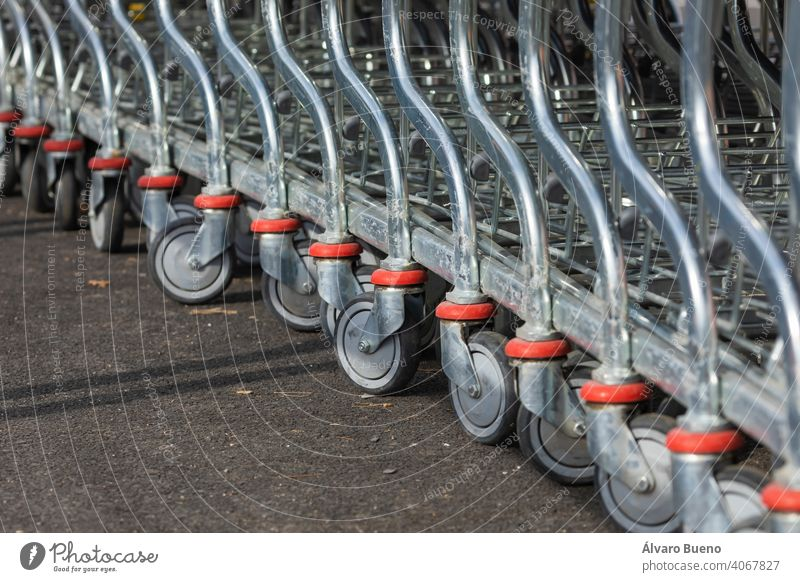 Shopping carts arranged in the parking and entrance area of a giant warehouse supermarket, on the outskirts of Zaragoza city, Spain. Aragon day cloudy sun