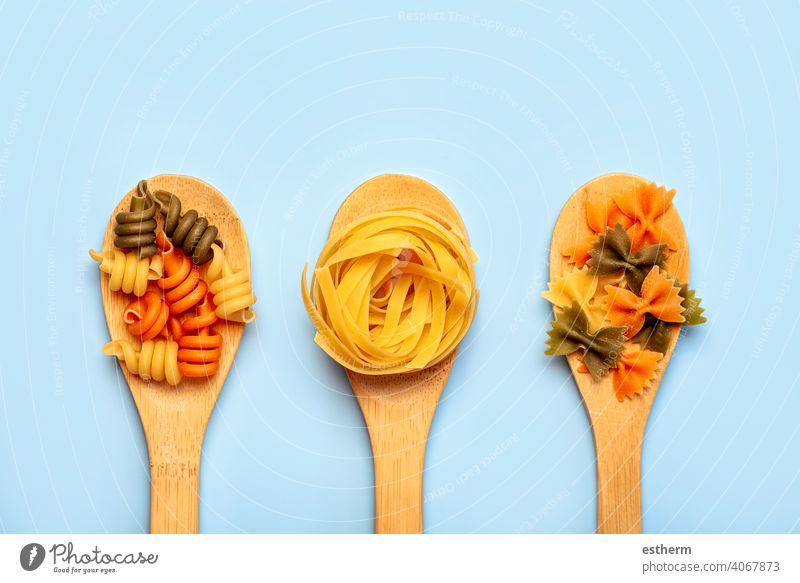 Different raw pasta types in three wooden spoons food eat diet dinner meal meat fresh restaurant menu italy food culinary spagetti tortellini italian cuisine