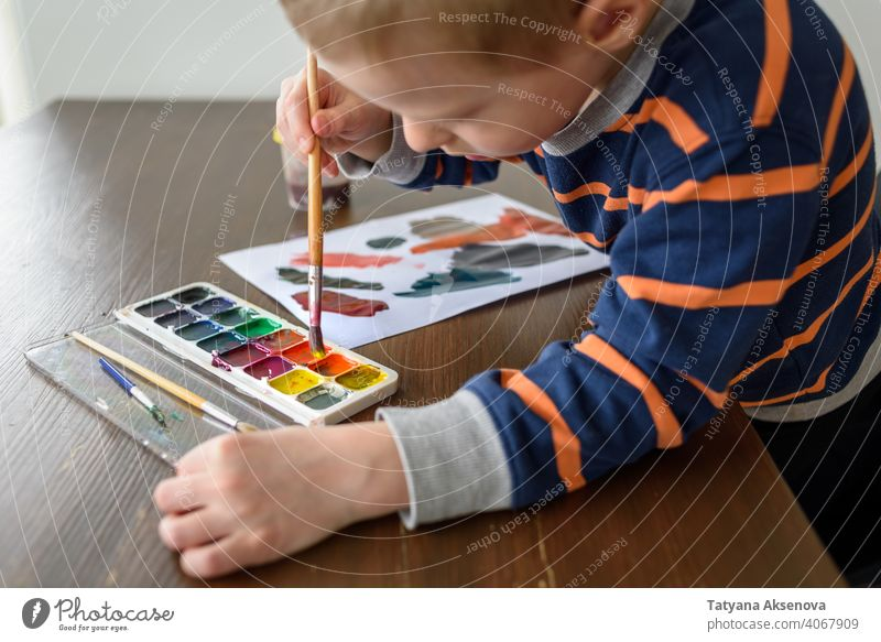 Little boy painting with watercolor child drawing artist hobby paintbrush painter creativity person hand paper young white artwork leisure imagination picture