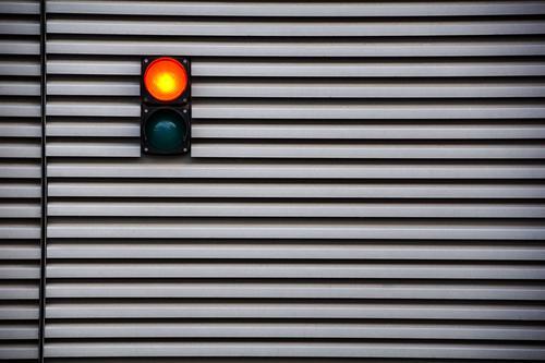 Red! says the traffic light at the garage door. Traffic light Light Lamp Stripe Garage Goal Tin Metal Exterior shot Garage door Colour photo Deserted