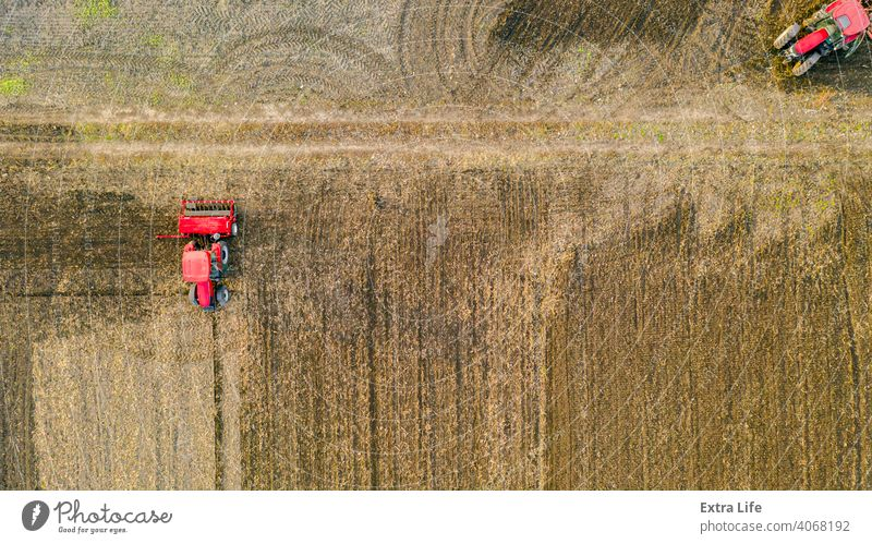 Above top view shot of three tractors, they are pulling machines, over arable field, preparing soil for new crop Aerial Agricultural Agriculture Agriculturist
