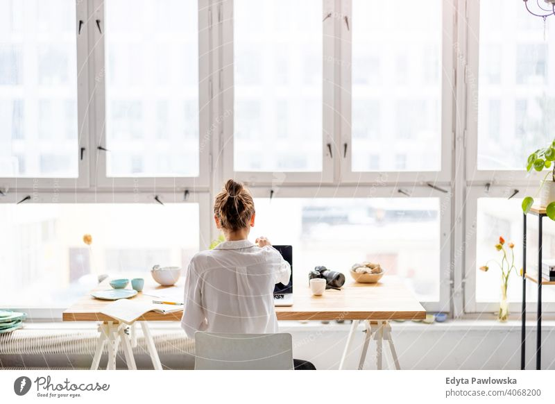 Rear view of young woman working on laptop in loft office millennials student hipster indoors window natural girl adult one attractive successful people