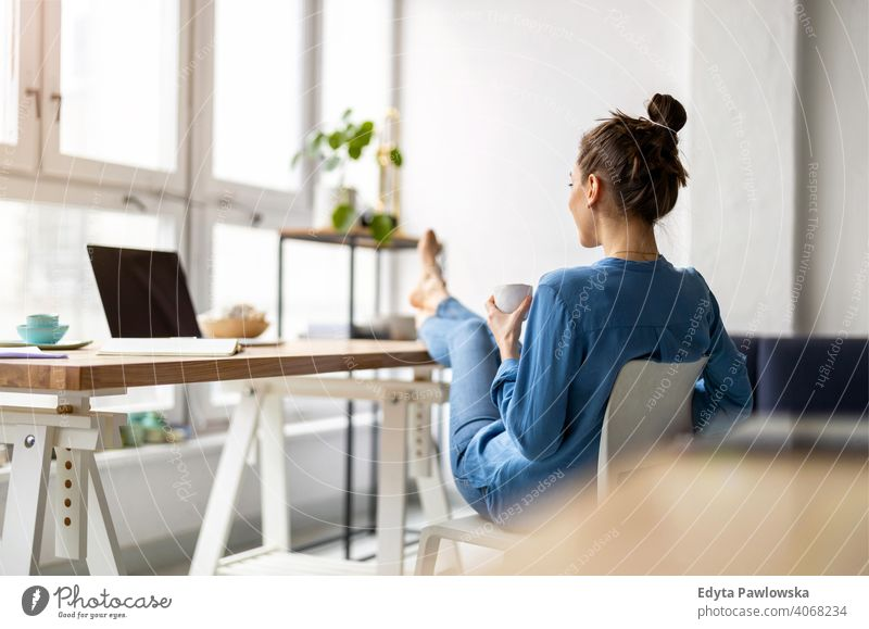Young woman relaxing in office with her bare feet on desk millennials student hipster indoors loft window natural girl adult one attractive successful people