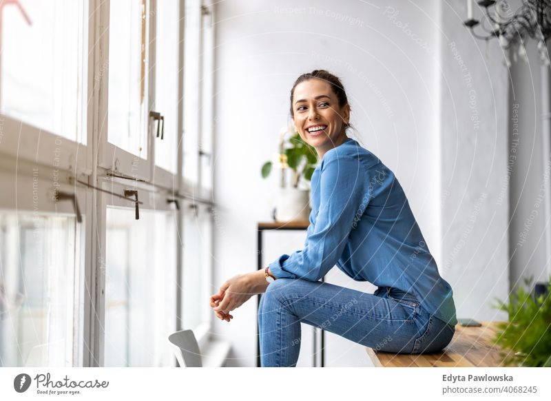 Portrait of a smiling creative woman in a modern loft space millennials student hipster indoors window natural girl adult one attractive successful people