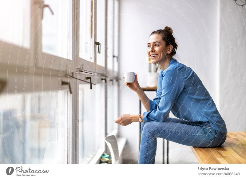 Young woman drinking coffee and looking out of a window millennials student hipster indoors loft natural girl adult one attractive successful people confident