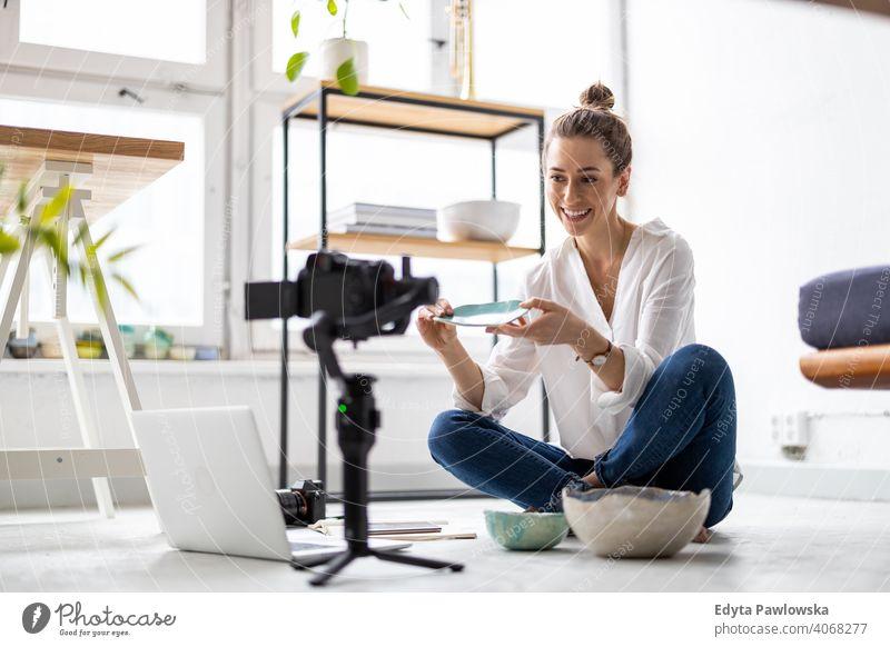 Female vlogger making social media video about her pottery laptop internet online computer technology shop retailer items workshop selling sitting floor