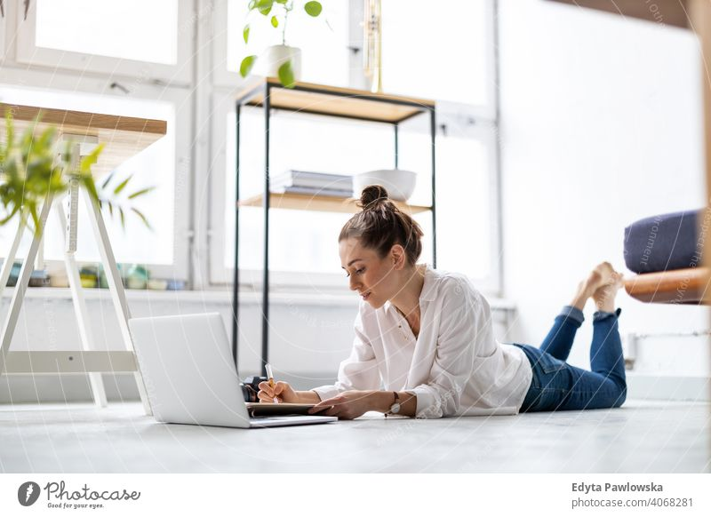 Creative young woman working on laptop in her studio millennials student hipster indoors loft window natural girl adult one attractive successful people
