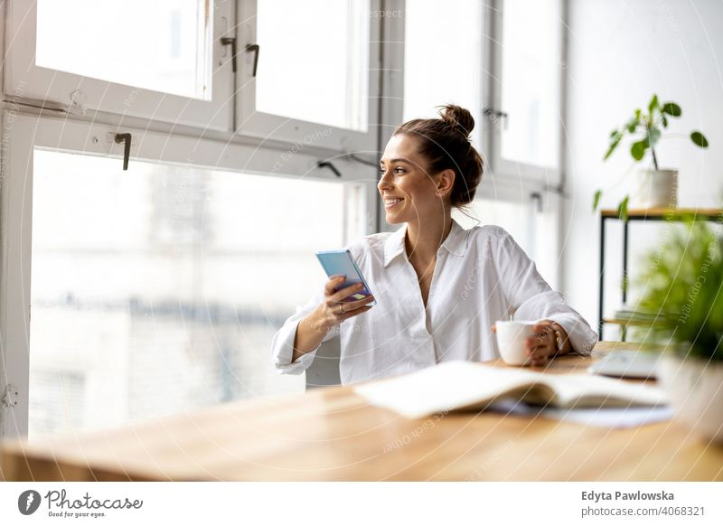 Creative business woman using smartphone in loft office millennials student hipster indoors window natural girl adult attractive successful people confident