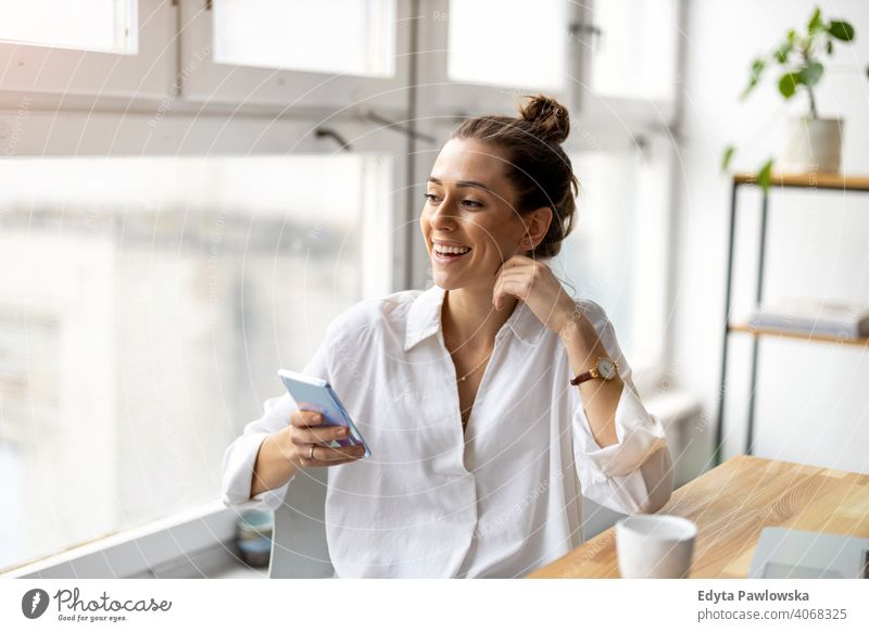 Shot of a young businesswoman using smartphone in an office millennials student hipster indoors loft window natural girl adult attractive successful people