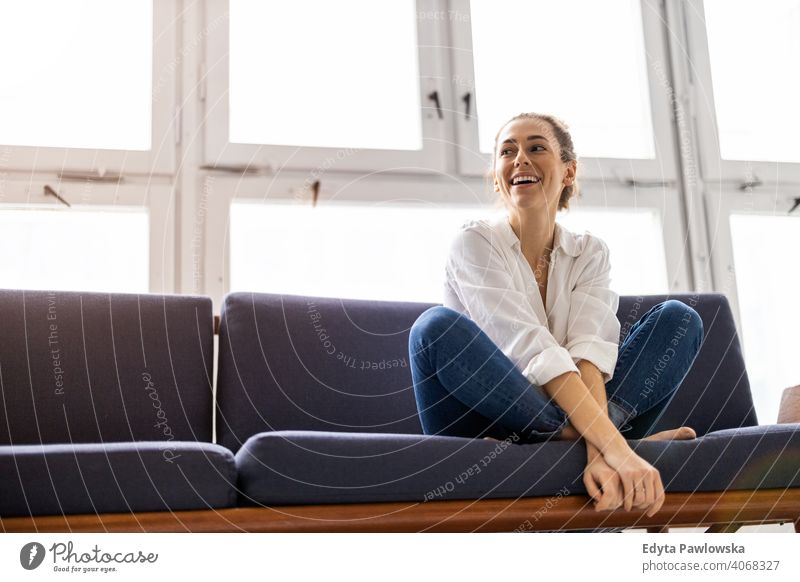 Young woman relaxing on sofa sitting couch resting comfortable break barefoot lotus yoga meditation millennials student hipster indoors loft window natural girl
