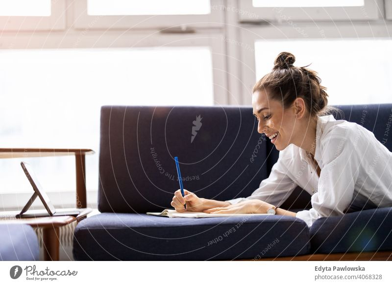 Young woman doing homework on sofa sitting couch resting relaxing comfortable millennials student hipster indoors loft window natural girl adult one attractive