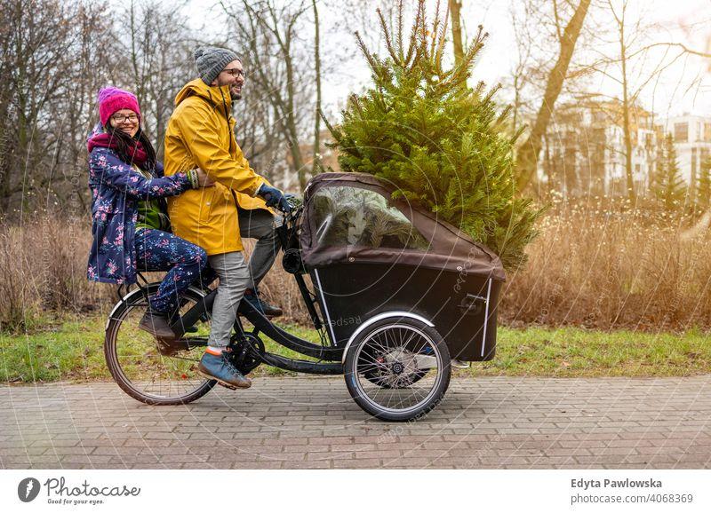 Couple having a ride with cargo bike transporting Christmas tree sustainable transport fun joy enjoying hipster modern carrying millennial winter ecologic