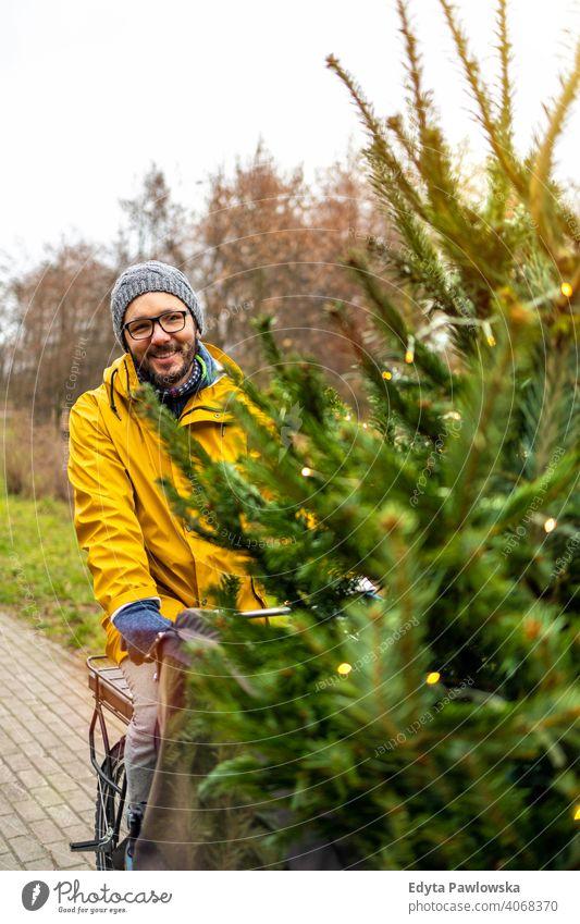 Man transporting Christmas tree on bicycle sustainable transport fun joy enjoying hipster modern carrying millennial winter ecologic ecology carbon footprint