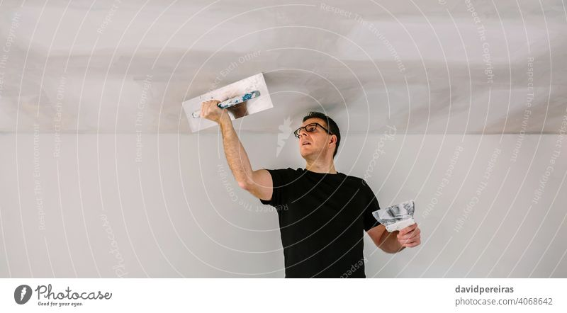 Plasterer smoothing plaster ceiling with the trowel banner plasterer gypsum board gypsum plaster installation working masonry drywall panoramic construction man