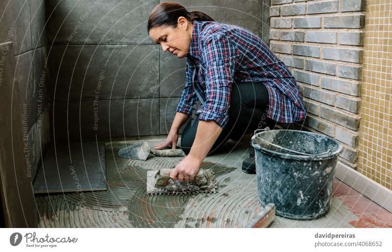 Female mason laying tiles on a terrace woman workman tiling floor imitation cement tile spread tiler glazed terrace working construction tool installing
