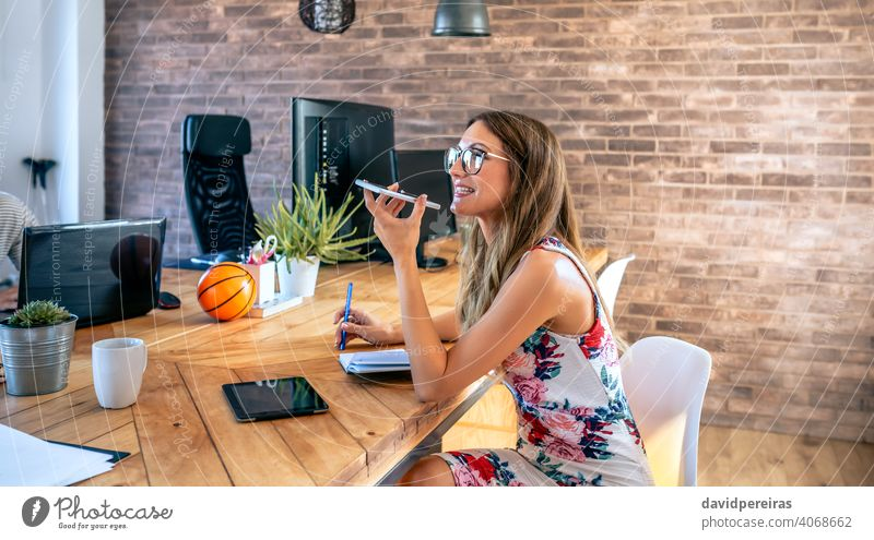 Office worker talking mobile phone with speaker businesswoman office worker talking speaker cell phone communication conversation people professional team young