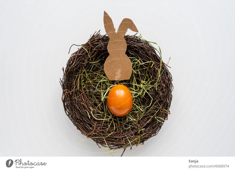 A paper Easter bunny and an Easter egg in a nest Nest Easter Bunny Paper Self-made white background plan Colour photo Easter egg nest Tradition Studio shot Egg