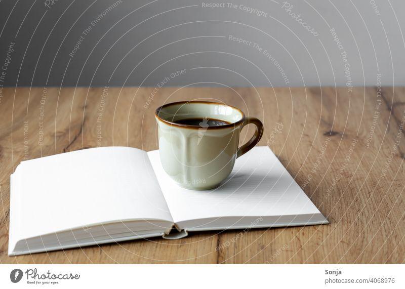 A rustic coffee cup on an open book Coffee Cup Book Open Beverage Coffee break Breakfast Aromatic Morning Hot Brown Old Caffeine Espresso Table Enamel Black