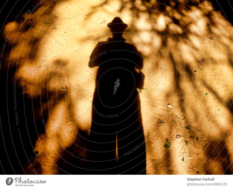 Eerie picture of a shadow man on sandy ground Shadow woman couple occult orange black dark darkness eerie shapes yellow creepy scary light night brown dream