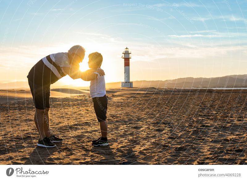 Grandfather and grandson hugging on a beach with a lighthouse in the background boy child childhood children coast dad day elderly family fangar far del fangar