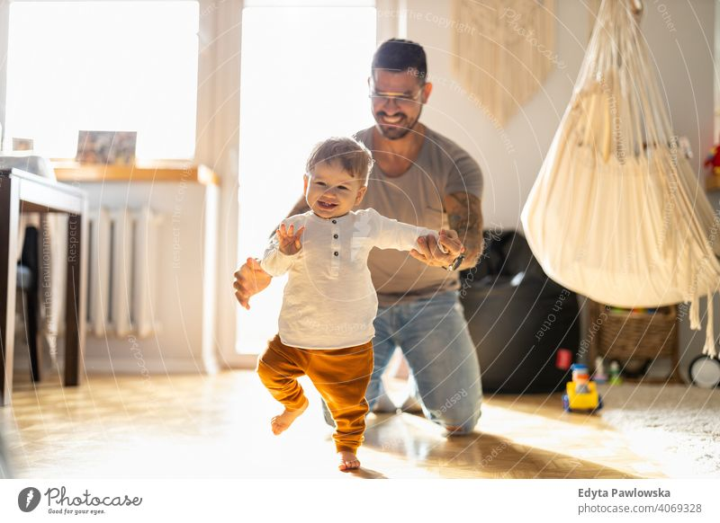 Little boy learning to walk with his father next to him at home single parent single dad fathers day fatherhood stay at home dad paternity leave modern manhood