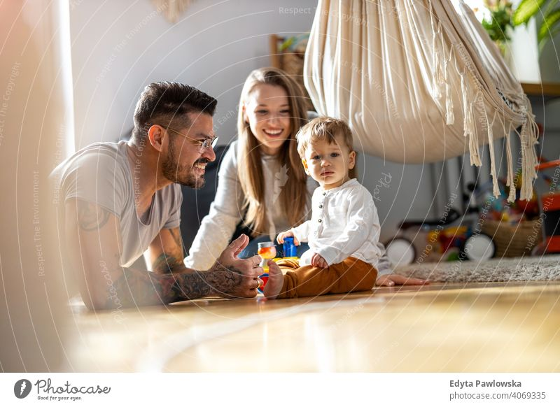 Young family having fun together at home father son child house girl adorable toddler parenting room daughter apartment handsome playing playful infant small