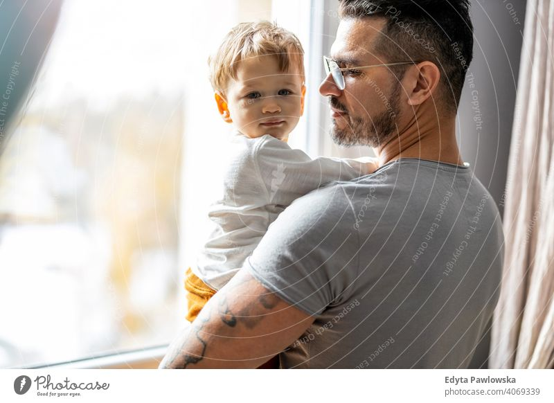 Dad holding his child in his arms at home single parent single dad fathers day fatherhood stay at home dad paternity leave modern manhood family son house girl